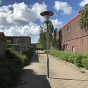 A walkway besides a red brick building with multiple streetlights